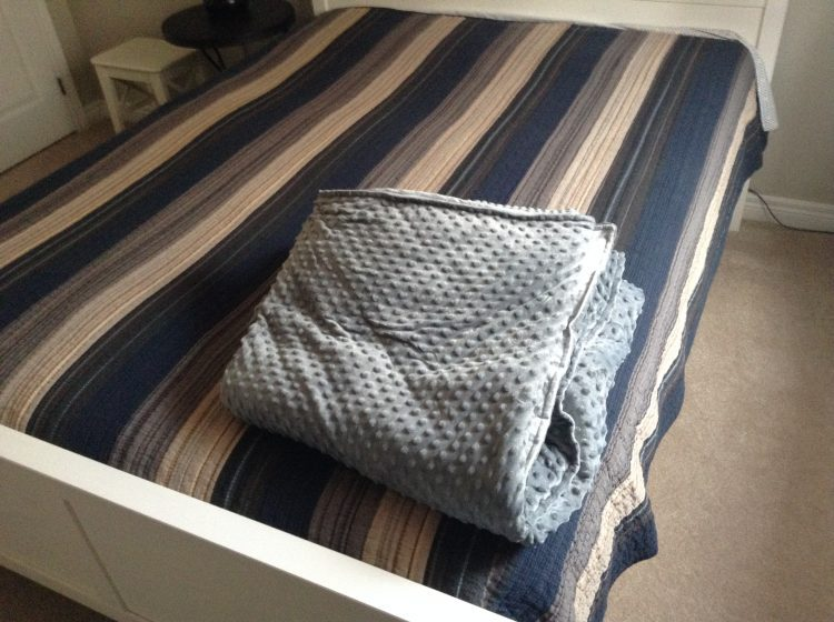 folded weighted blanket on bed